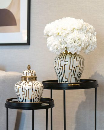 White hydrangea faux flower display in gold and white ginger jar